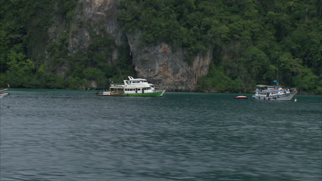 stockvideo's en b-roll-footage met exterior shots from a tourist boat sailing into koh phi phi islands past anchored yachts and island hills on august 26 2014 in thailand - voor anker gaan