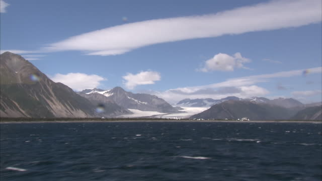 exterior shots from aboard a boat in the gulf of alaska as it travels alongside the snow-capped mountains and cliffs of the kenai peninsula on a... - kenai peninsula stock videos & royalty-free footage