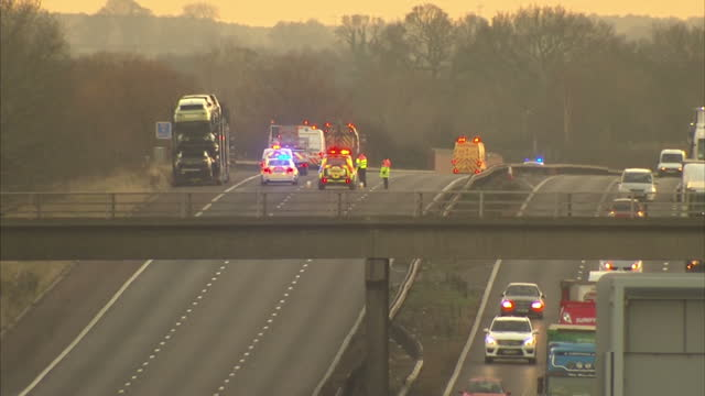 Exterior shots from bridge over M6 of emergency services vehicles Parked car transporter on southbound carriageway at dusk Exterior shots civilian...