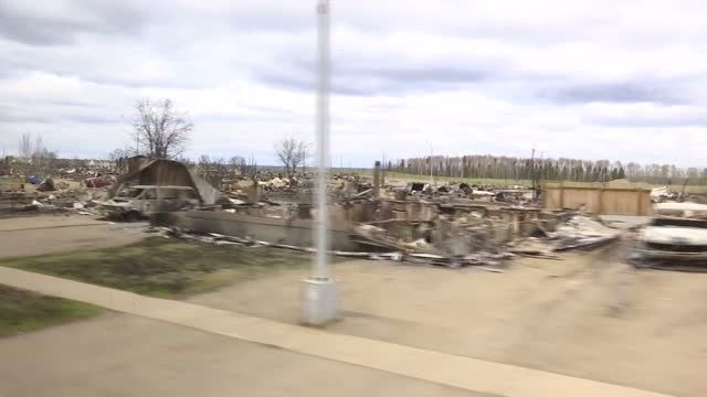 Exterior shots from car driving past burnt out homes and cars after wildfire on May 10 2016 in Alberta Canada