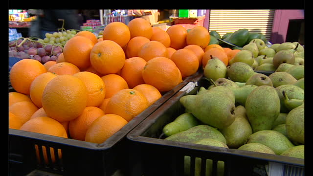 exterior shots fruit & vegetables on display at outdoor market stall. exterior shots market traders at the fruit & veg stall dealing with customers... - 1 minute or greater stock videos & royalty-free footage