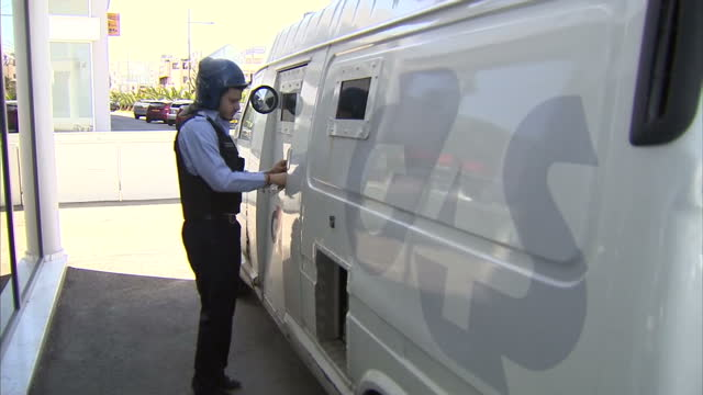 exterior shots g4s bank security worker delivery cash packages to bank from delivery slots in van exterior shot g4s van departs banks in cyprus open... - ユーロ圏債務危機点の映像素材/bロール
