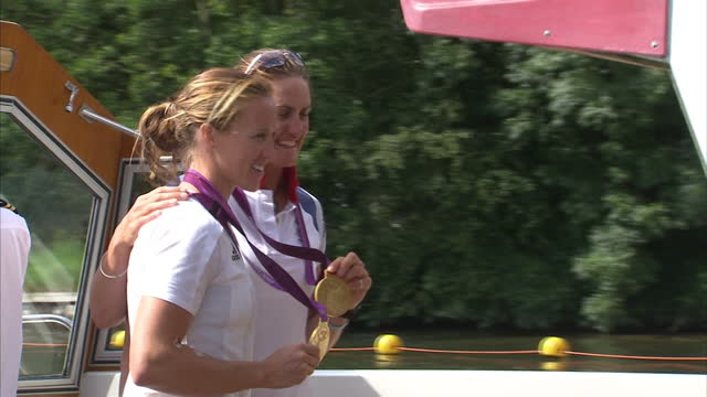 exterior shots gb's gold winning rowing pair helen glover heather stanning pose for snappers on boat holding their gold medals gb's gold medal... - helen glover rower stock videos and b-roll footage