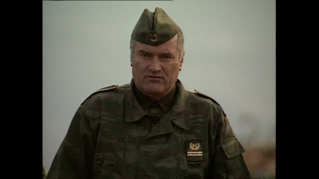Exterior shots General Ratko visiting countryside hilltop outpost with heavy artillery guns and greets BosnianSerb soldiers before getting into...