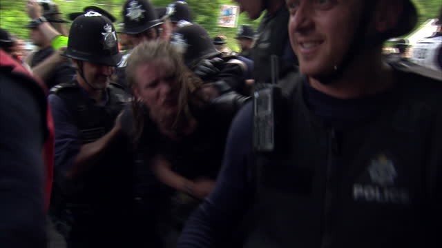 exterior shots general views police officers marching forward with arrested anti fracking protester in middle of police lines police arrest anti... - protesta anti fracking video stock e b–roll