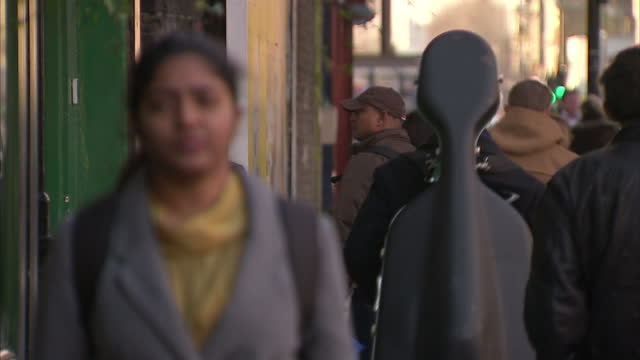 exterior shots generic street scenes with people walking along the high street in bethnal green. exterior shots black police officer stood on the... - multiculturalism stock videos & royalty-free footage