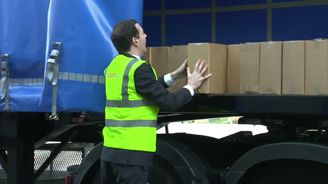 exterior shots george osborne chancellor of the exchequer on visit to freight first helping workers to pack boxes onto lorry on march 27 2015 in... - チャンセラー点の映像素材/bロール