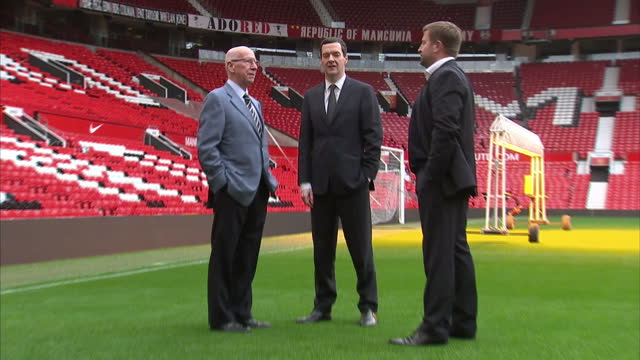 exterior shots george osborne chancellor of the exchequer standing talking on old trafford pitch with sir bobby charlton and richard arnold managing... - チャンセラー点の映像素材/bロール