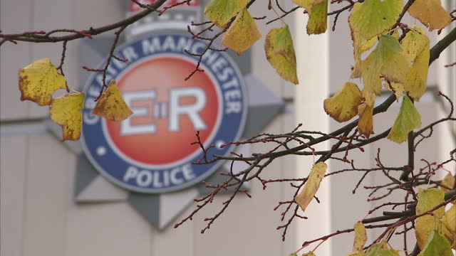 Exterior shots Greater Manchester Police crest on front of police headquarters building on in Manchester England