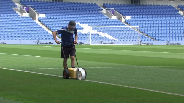 exterior shots groundsmen painting pitch markings onto grass at falmer stadium home to brighton and hove albion football club on january 21 2016 in... - ground staff stock videos & royalty-free footage