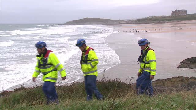 exterior shots hm coastguard search and rescue workers patrolling along coastal path overlooking beach with swimmers and surfers in sea at scene... - 見渡す点の映像素材/bロール