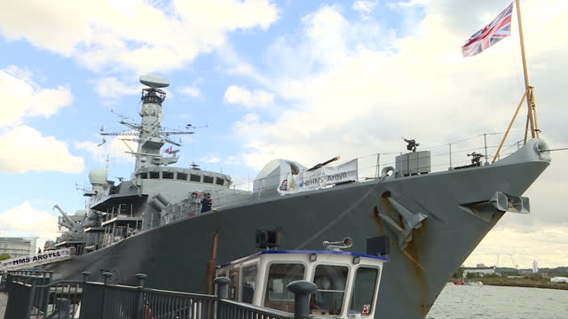 Exterior shots HMS Argyll Type 23 'Duke' Class frigate with Union Jack billowing against sky