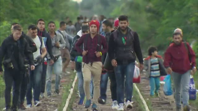 Exterior shots hundreds of migrant refugees inc families walk along train tracks carrying their belongings on September 07 2015 in Roszke Hungary
