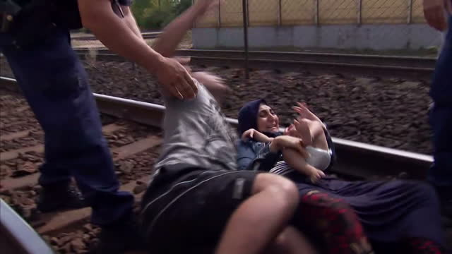 Exterior shots Hungarian riot police forcibly separate migrant refugee man from wife and baby who are lying on the rail tracks screaming after train...