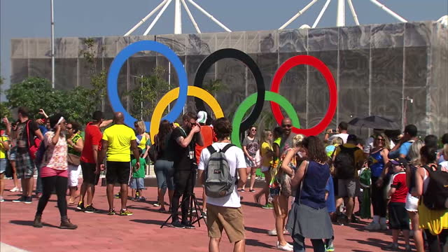 exterior shots international flags flying at the barra olympic park and people having photos taken in front of large olympic rings on the final day... - 記号点の映像素材/bロール