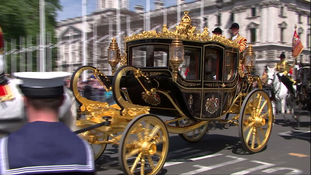 exterior shots irish state coach passing carrying the queen to parliament escorted by members of the household cavalry and followed by procession of... - the queen's speech state opening of uk parliament stock-videos und b-roll-filmmaterial