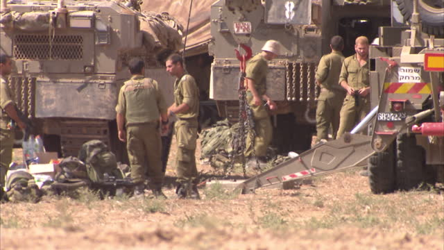 stockvideo's en b-roll-footage met sderot exterior shots israeli idf troops in olive green fatigues next to tanks and apc's armoured personnel carriers making preparations for ground... - israëlisch leger