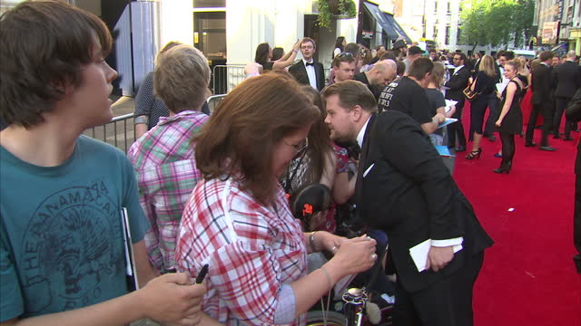 Exterior shots James Corden signing autographs and posing for photographs on BAFTA red carpet on May 18 2014 in London England