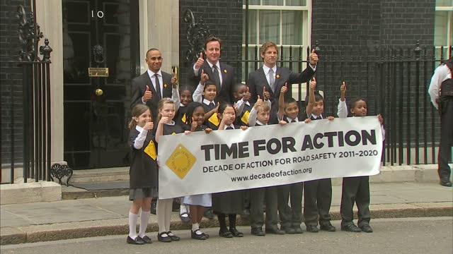 Exterior shots Jenson Button Lewis Hamilton Prime Minister David Cameron pose for photo call with group of children holding TIME FOR ACTION on road...