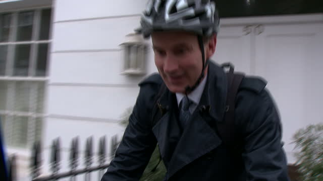 Exterior shots Jeremy Hunt Health Secretary cycling away and ignoring reporters re NHS cyber attack and failing to take action over vulnerable NHS...