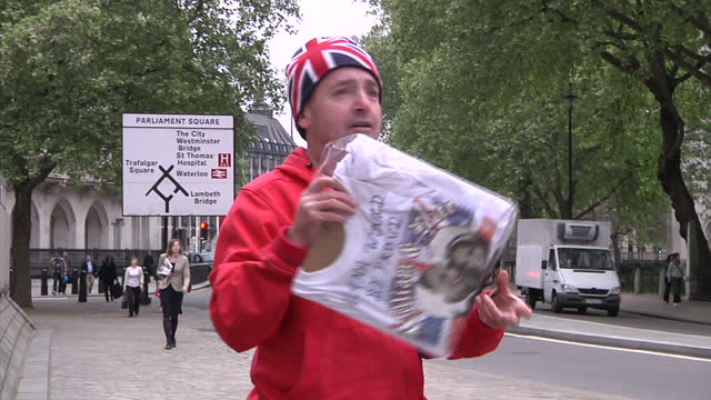 exterior shots john loughrey unpacking his union flag patriotic dress including royal memorabilia tshirts as he stakes his place opposite westminster... - souvenir stock videos and b-roll footage