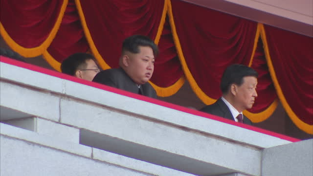 Exterior shots Kim JongUn North Korean Leader waving to crowds as float carrying large image of his father Kim Jongil passes during Workers Party...