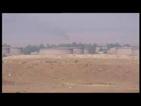 vidéos et rushes de exterior shots kirkuk oil field, oil facility in desert. exterior shots of flame burning at facility. exterior shots of oil facility as traffic... - 50 secondes et plus