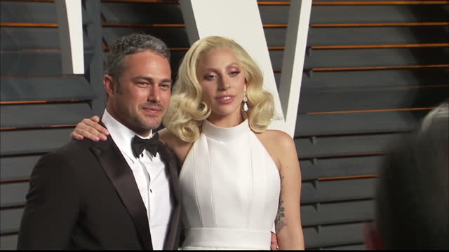 Exterior shots Lady Gaga and Fiance Taylor Kinney actor on Vanity Fair red carpet posing for photographers on February 28 2016 in Hollywood California