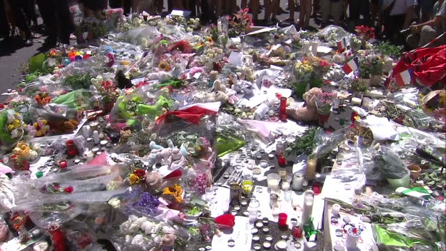 exterior shots large collection of flowers and candles on ground with crowd of mourners at the scene of Nice truck terror attacks Shot on July 16...