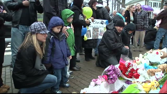 exterior shots large crowd of mourners stood around christmas tree looking at the mass of truibutes flowers cuddly toys crowds of mourners at newtown... - newtown connecticut stock videos & royalty-free footage