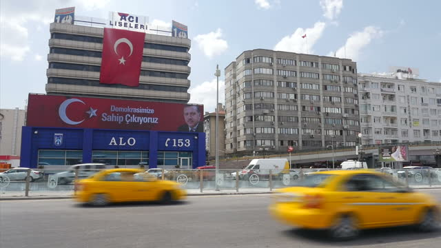 Exterior shots large LED screen on front of building showing images of Turkish President Recep Tayyip Erdogan and message reading 'We turn out we...