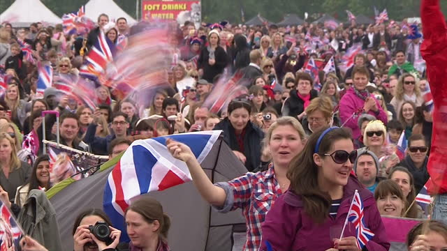 Exterior shots large video screen in Hyde Park showing the Royal Wedding coverage with hundreds of people waving Union flags cheering loudly Exterior...