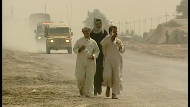 exterior shots local iraqi men walking at side of road as british military convoy passes along road at the start of the 2003 invasion of iraq on... - bassora video stock e b–roll