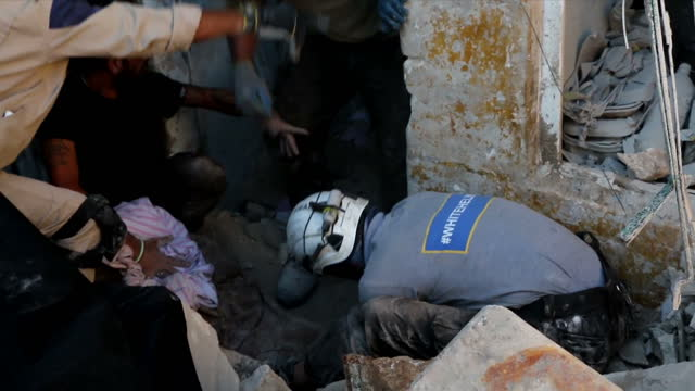 Exterior shots local people and emergency workers White Helmets r searching through rubble of collapsed building digging out victims of air strike on...