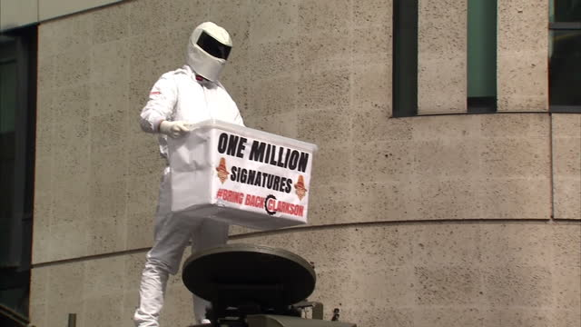 exterior shots man dressed as top gear's the stig standing on top of military tank outside bbc new broadcasting house showing 'bring back clarkson'... - petition stock videos & royalty-free footage