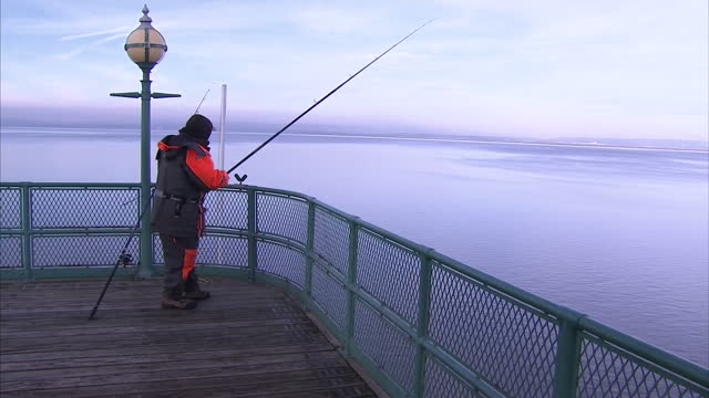 exterior shots man fishing on clevedon pier. on december 20, 2016 in clevedon, united kingdom. - clevedon pier stock videos & royalty-free footage