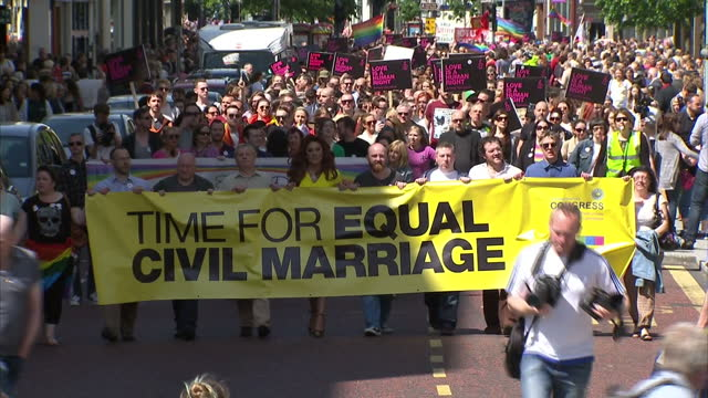 Exterior shots march rally through Belfast City Centre people holding Time for Equal Civil Marriage banner and Love is a Human Right placards on June...