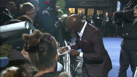 exterior shots marlon sanders posing for cameras on red carpet and signing autographs for fans - 親筆簽名 個影片檔及 b 捲影像