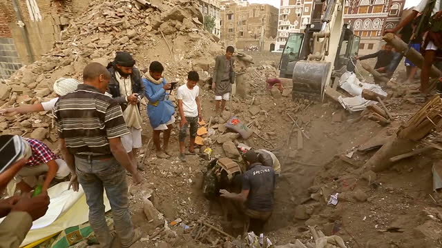 Exterior shots men attempting to pull body out of ditch in rubble and men carrying person on stretcher down street on June 15 2015 in Sana'a Yemen