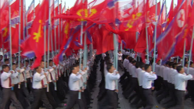 Exterior shots men in shirts and red ties marching carrying the North Korean flag and the flag of The Workers Party of North Korea during Workers...
