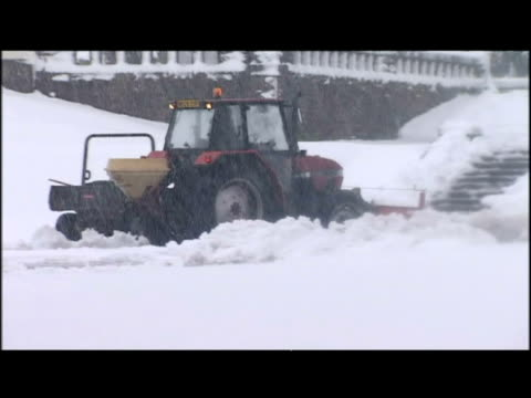 exterior shots men walking across slushy road carrying shovels tractor clearing snow exterior shots countryside road under blanket of snow with cars... - fanghiglia video stock e b–roll