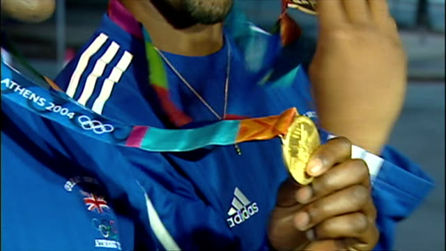 exterior shots men's 4 x 100m olympic relay team posing with gold medals darren campbell marlon devonish jason gardner and mark lewisfrancis on... - testimone ruolo dell'uomo video stock e b–roll