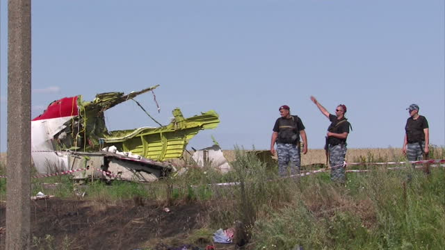exterior shots mhc workers carry body bag from mh17 crash site - ロシア軍点の映像素材/bロール