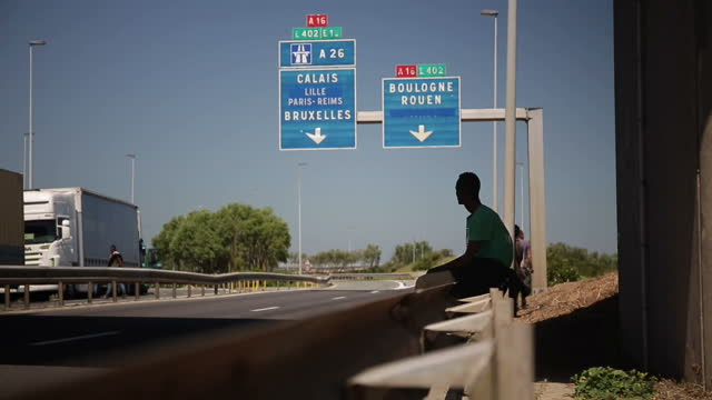 exterior shots migrant sitting on barrier at the side of the motorway watching lorries stopped in tailback due to strikes at calais port on june 30... - calais stock videos and b-roll footage