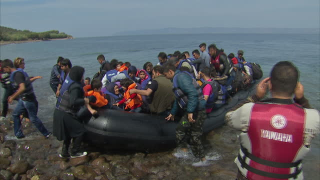 exterior shots migrants arrive on lesbos beach in packed dinghy and are helped to shore by volunteers on september 09 2015 in lesbos greece - 逃げる点の映像素材/bロール