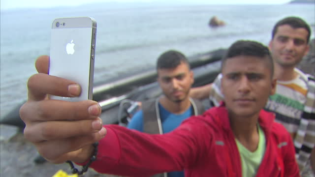 exterior shots migrants on lesbos beach talking selfies with mobile phones on september 09 2015 in lesbos greece - 2015 stock-videos und b-roll-filmmaterial