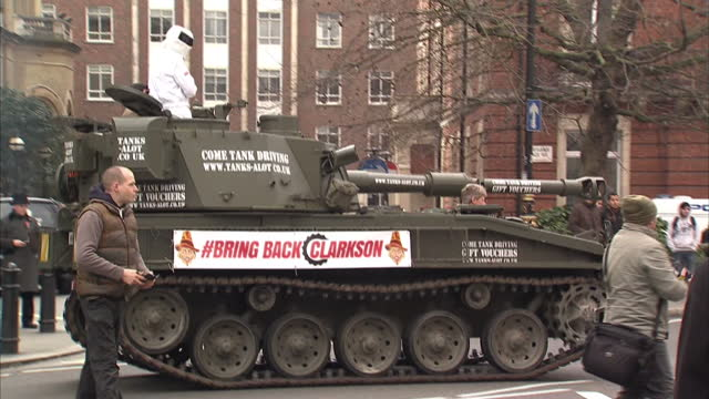 exterior shots military tank approaching bbc new broadcasting house with man dressed as the stig riding on top along with harry cole coeditor of... - petition stock videos & royalty-free footage