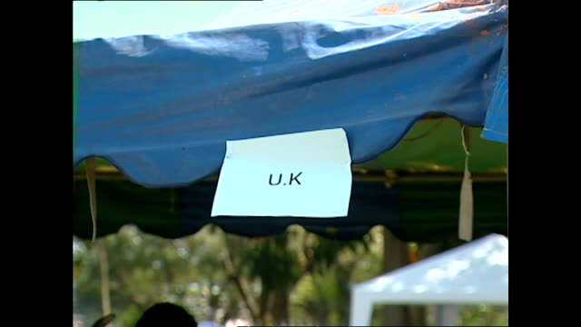 exterior shots missing persons centre people registering at stalls piles of red cross bags at information centre women unpacking food aid people... - indian ocean stock videos & royalty-free footage