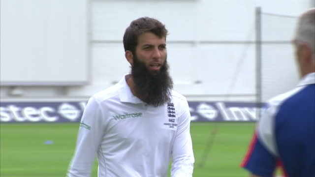 exterior shots moeen ali, england cricket player walking across pitch at swalec stadium for team photo ahead of first ashes test match. on july 07,... - チーム写真点の映像素材/bロール