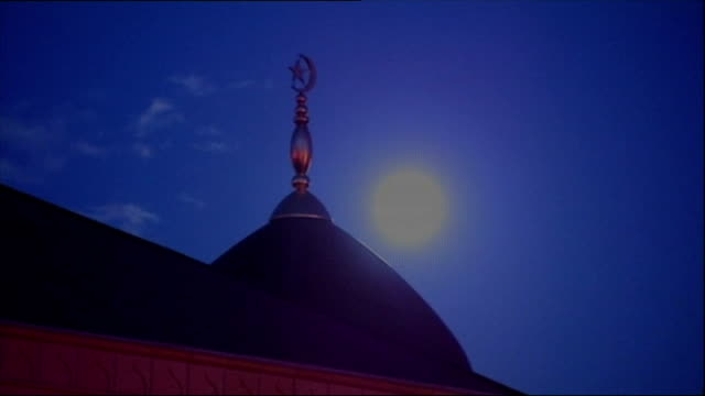 Exterior shots Mosque dome crescent moon and star symbol in silhouette against night sky and clouds on November 17 2005 in Bradford England
